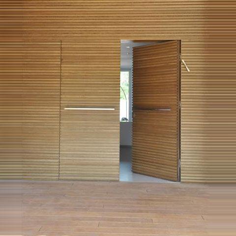 דלת כניסה כפולה בציפוי עץ עם ציפוי קיר מעץ